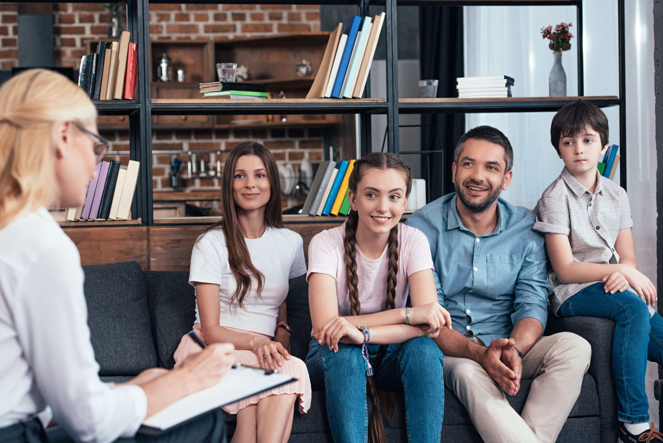 Tiny Smiling Family on Therapy Session by Female Counseling