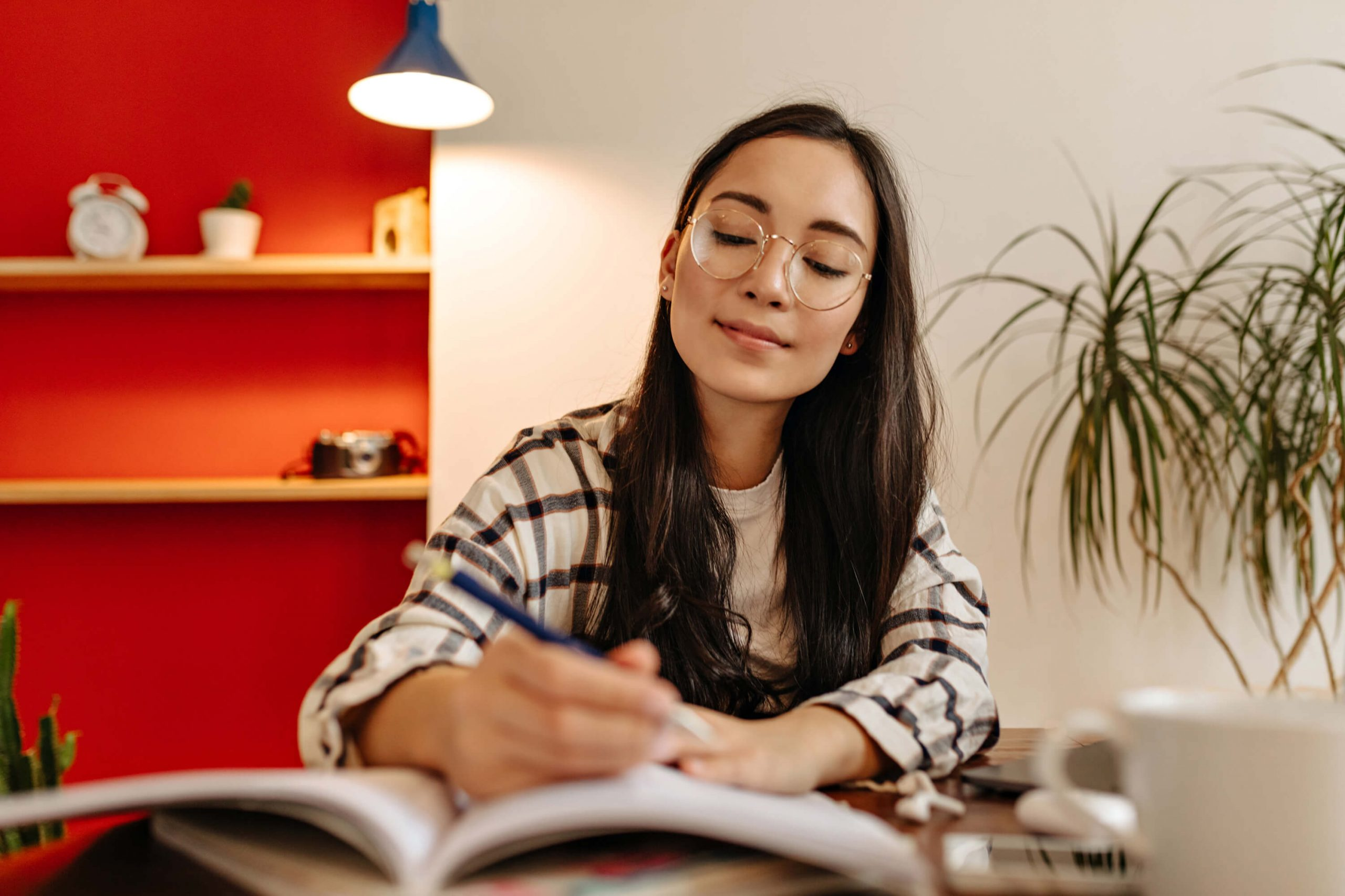 joyful woman in plaid shirt takes notes in journal